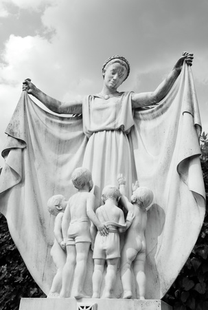 monumental cemetery: marble antique statue symbolizing mother protecting her children, monumental  cemetery in Florence, Italy Stock Photo
