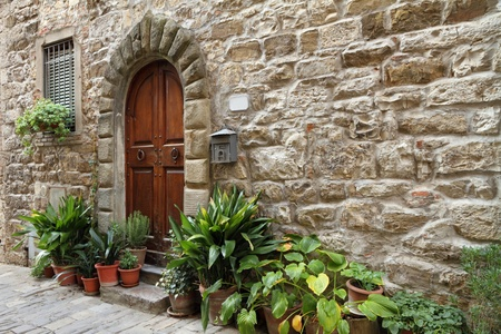 stony antique wall with framed arc door in italian village, Tuscany, Montefioralle photo
