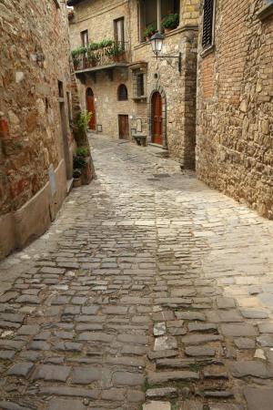 vintage: smalle steenachtige straat in de Italiaanse middeleeuwse dorp Montefioralle, Toscane, Europa