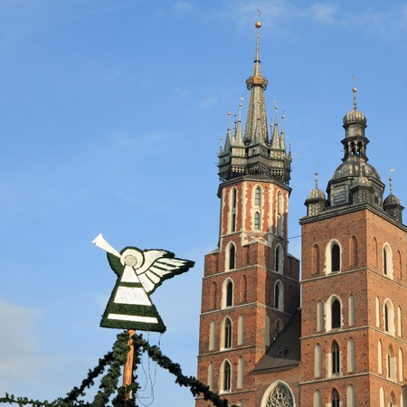 playing the market: christmas decorations with playing on trumpet angel  on Main Market Square in Krakow during xmas and new year time, at the background Mariacki Church, Cracow, Malopolska, Poland, Europe