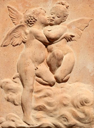 two kissing angels relief in tuscan terracotta, Italy photo