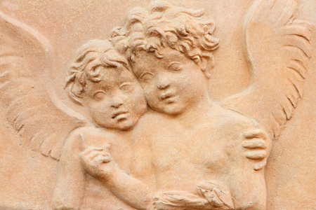 two angels holding together - terracotta relief photo