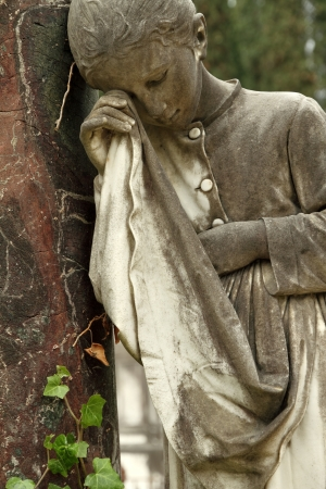 crying girl: detail of tomb with crying girl statue, monumental cemetery in Italy, Europe  Stock Photo