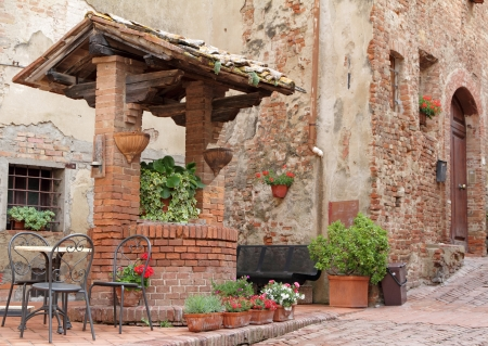 brick old well decorated with plants and flowers on italian street in tuscan borgo Certaldo, Italy, Europe Standard-Bild