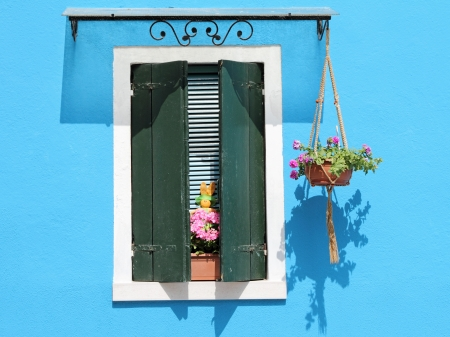 burano: colorful facade with window with shutters, typical vivid colors for village Burano on venetian lagoon, Italy, Europe