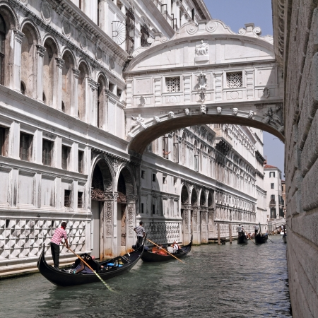 Gondolas passing over Bridge of Sighs - Ponte dei Sospiri. A legend says that lovers will be granted eternal love if they kiss on a gondola at sunset under the Bridge. Venice,Veneto, Italy, Europe.