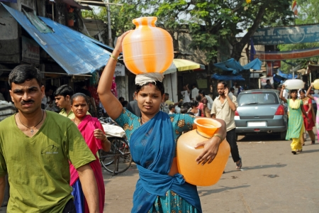 MUMBAI, INDIA - NOVEMBER 26: Indian woman carry water jugs in India on Nov.26, 2010 in Mumbai. Collecting and carrying water are womens responsibilities in India.