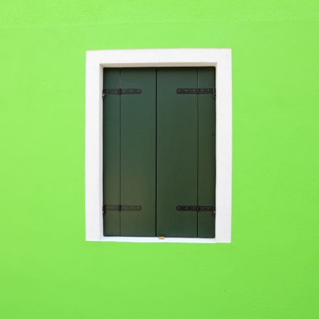 detail of vivid green facade with window with closed shutters, Burano, Venice, Italy, Europe photo
