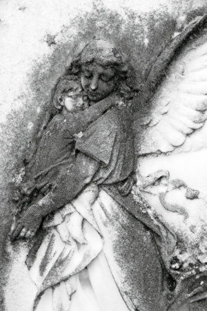angel holding a child, antique relief  on Monumental Cemetery in Florence, Italy, Europe photo