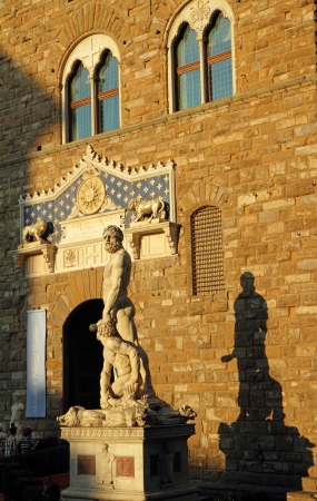 facade of Palazzo Vecchio in Florence at sunset light and Hercules and Cacus statue by Baccio Bandinelli, Piazza Signoria, Florence, Italy, Europe photo