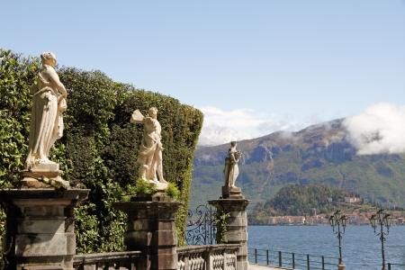 bellagio: antique statues and hedge as fencing of historic Villa Carlotta in Tremezzo on lake Como, at horizon village Bellagio, Lombardy, Italy, Europe