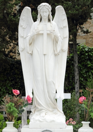 angel headstone: angel holding cross, tomb on monumental cemetery in Italy, Florence, Europe