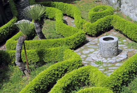 formal garden: ornamental  garden with hedges  and antique well, Garden of Villa Monastero in Varenna on lake Como, Lombardy, Italy, Europe