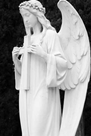 image of angelic sculpture holding a cross, monumental cemetery in Italy, Europe photo