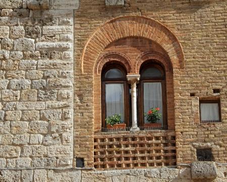 tuscan house: beautiful old window with arc and column, San Gimignano, Tuscany, Italy, Europe