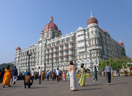 MUMBAI, India - NOVEMBER 27 Tourists in front of the Taj Mahal Palace,famous for combining Islamic and European Renaissance architecture  Its 565 rooms are in Moorish, Oriental, and Florentine styles