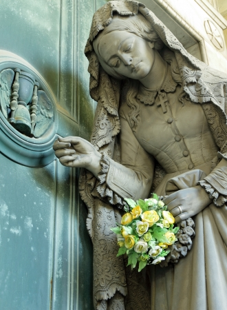 monumental cemetery:  suffering woman with flowers - detail of antique tomb on monumental cemetery in Italy, Staglieno, Genova, Europe