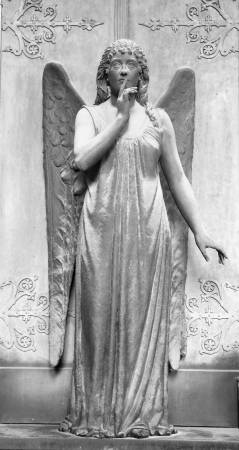 angelic figure in front of the tomb with gesture of silence , monumental cemetery of Staglieno, Genova, Italy, Europe