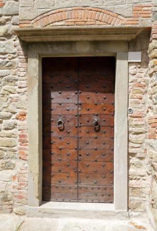 vintage double wooden door with studs and antique brick and stone wall,  Cortona, Tuscany, Italy, Europe photo
