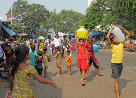 poverty in india: MUMBAI,INDIA-NOVEMBER 26 Children carrying water on Nov 26, 2010 in Mumbai  Poor children in India begin working at a very young and tender age  Many children have to work to help their families