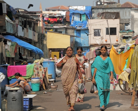 poverty india: MUMBAI, INDIA-NOV 27  Women in district of slums on Nov  27,2010 in Mumbai Growth in urban population has resulted in a large section of  population living in abject poverty in overcrowded slums  Editorial