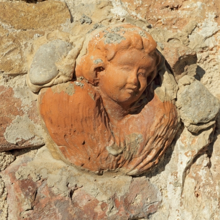 angel figurine: head of angel in tuscan terracotta  on antique stone wall in Tuscany, Italy, Europe Stock Photo