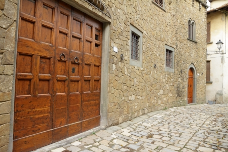 elegant big double doorway facade of old houses in medieval tuscan village, Montefioralle, Greve in Chianti, Italy, Europe