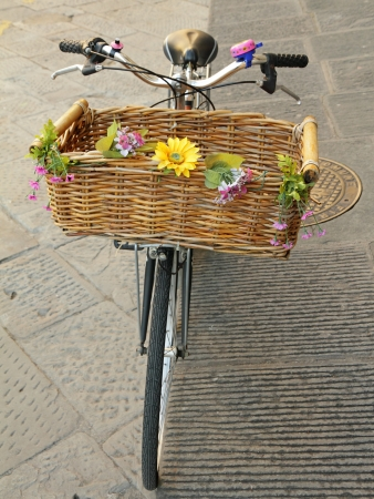 parked bicycles: vintage bike with straw basket with flowers, Florence, Europe