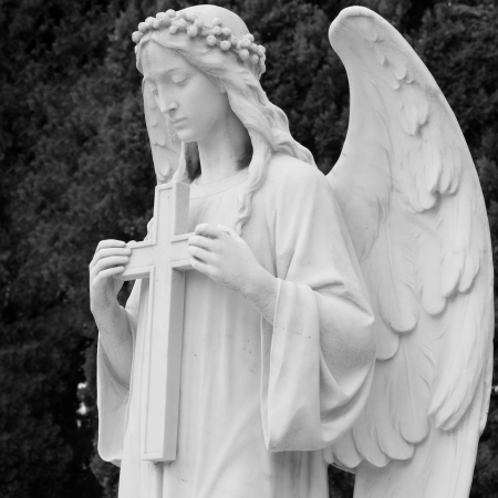 monumental cemetery: image of angel  holding a cross, detail of historic tomb on monumental cemetery in Italy, Europe
