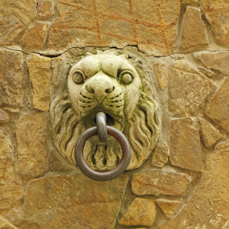 heads old building facade: beautiful medieval handle on wall  to fasten horse, Tuscany, Italy, Europe