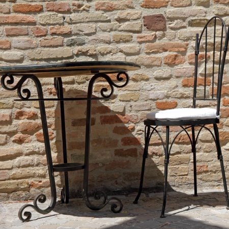 round chairs: wrought iron chair and table on sunny terrace, Italy,  Europe
