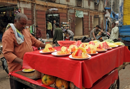 MUMBAI, INDIA-NOV 22 Vendor  sells fruit salad in a street on Nov  22,2010 in Mumbai  According to the Food and Agriculture Organization, 2 5 billion people eat street food every day  Stock Photo - 17586019