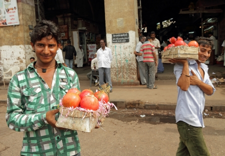 market vendor: MUMBAI,INDIA-NOV 22 Vendors sell pomegranate fruits  in a street on Nov  22,2010 in Mumbai Agricultural sector makes up 18 1  of GDP  India is the biggest producer of fruits and second for vegetables