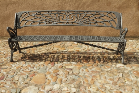 vintage metal bench on paved sidewalk, Spain, Europe photo