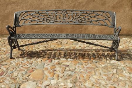 wrought iron: vintage metal bench on paved sidewalk, Spain, Europe