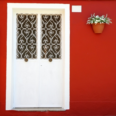 ornamental white double door and vivid red wall with hanging  flowerpot, Burano village on venetian lagoon, Venice , Italy, Europe photo