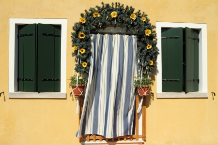cute doorway framed with garland wreath and striped door curtain in borgo Burano, Venice, Veneto, Italy, Europe Stock Photo - 21161036