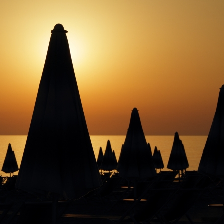 furled: silhouettes of many furled beach umbrellas on the beach on sunset time, Italy,Europe