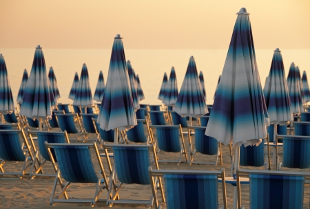 deck chairs: scene with closed blue and white striped  beach umbrellas and deck chairs at sunset time , Italy, Europe