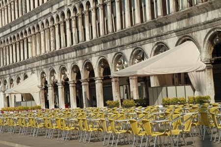 vecchie: Many empty tables and chairs on the early morning on Piazza San Marco with buildings of  the  Procuratie Vecchie, place of old, famous and expensive coffee houses as Caffe Quadri, Lavena Venice, Italy Stock Photo