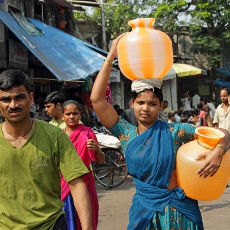 hombre pobre: MUMBAI, INDIA - 26 de noviembre mujer india lleva jarras de agua en la India el 26 de noviembre de 2010 en Mumbai recolecci�n y el transporte de agua son las mujeres