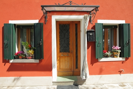 entrance to the typical vivid painted house with small roof over door on Burano island, Venice, Veneto, Italy, Europe Stock Photo - 21758536