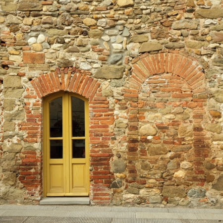 old brick and stone wall with door to the tuscan house, Anghiari, Italy photo