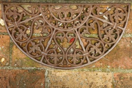 antique wrought iron doormat on brick floor, Tuscany, Italy photo