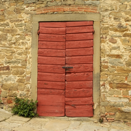 old wooden red gate and stonewall, detail of historic tuscan building, Italy, Europe photo