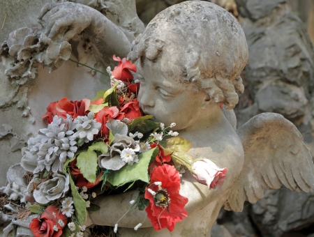 condolence: angelic sculpture with flowers , detail of beautiful tomb on monumental cemetery in Italy, Staglieno, Genova, Liguria, Europe Stock Photo