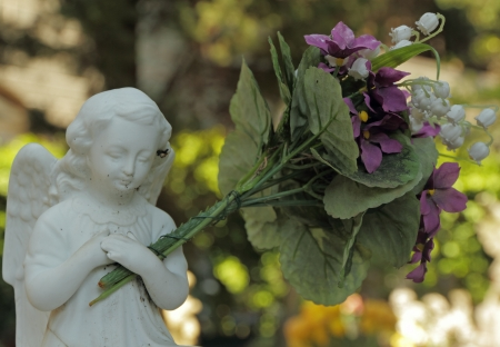 angel cemetery: little angel figure holding a huge bouquet of flowers on monumental cemetery, Staglieno, Genoa, Italy, Europe