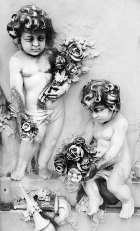 monumental cemetery: two little angels with flowers - relief on tomb on monumental cemetery San Michele in Venice, Italy, Europe