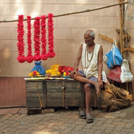 MUMBAI  - NOVEMBER 21  Man selling colorful flower garlands on November 21, 2010 in Mumbai, India  These floral garlands are offered to the gods in the temples