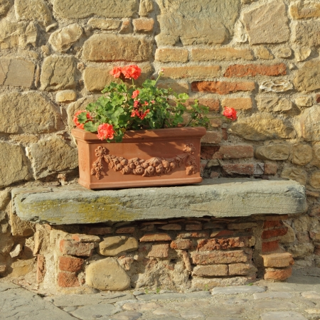 beautiful tuscan terracotta planter in front of  old stone and brick house, Italy, Europe photo
